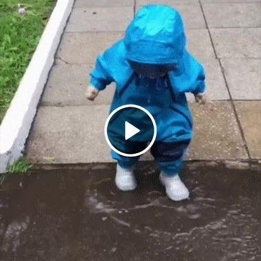 Criança se diverte com poça de água.