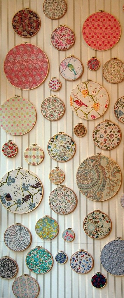 "Purl Soho  ""Create eclectic wall art using an array of fabric swatches and wooden embroidery hoops.  Pull the fabric taught in the hoop.  Run a line of glue on the inside of the hoop and press the fabric into the glue.  Allow the glue to dry and then trim excess fabric."""