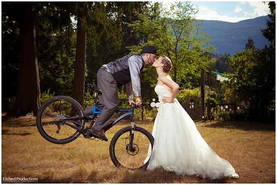 Groom on mountain bike kissing bride, photographed by Chuck Hocker of Etched Productions. www.etchedproductions.ca: