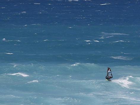 Wer sehnt sich hierzulande nicht danach: Türkisfarbenes Wasser und Sonne satt. Ein Windsurfer genießt das sommerliche Wetter (knapp 30 Grad) in Kapstadt, Südafrika, und lässt sich auf seinem Brett vom Wind treiben.