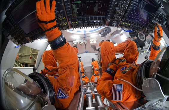 Spacesuit engineers demonstrate how four crew members would be arranged for launch inside the Orion spacecraft, using a mockup of the vehicle at Johnson Space Center. Credits: NASA/Robert Markowitz