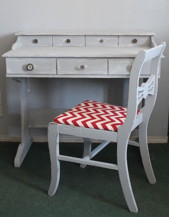 A desk painted gray with hints of dark wood and white. The chair has a