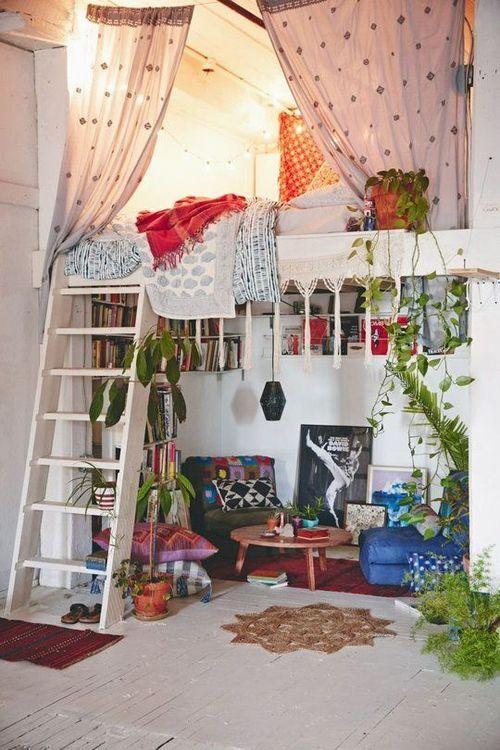 sala decorada no estilo boho chic, bohemiam chic com escada que dá acesso ao quarto com cortinas separando o ambiente, puffs e almofadas coloridas no chão