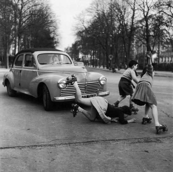 Robert Doisneau, Les patins à roulettes à La Muette, Paris, France, 1955.  (Une fillette en patin à roulettes tombe en traversant la rue sur la chaussée de la Muette à Paris en 1955.)