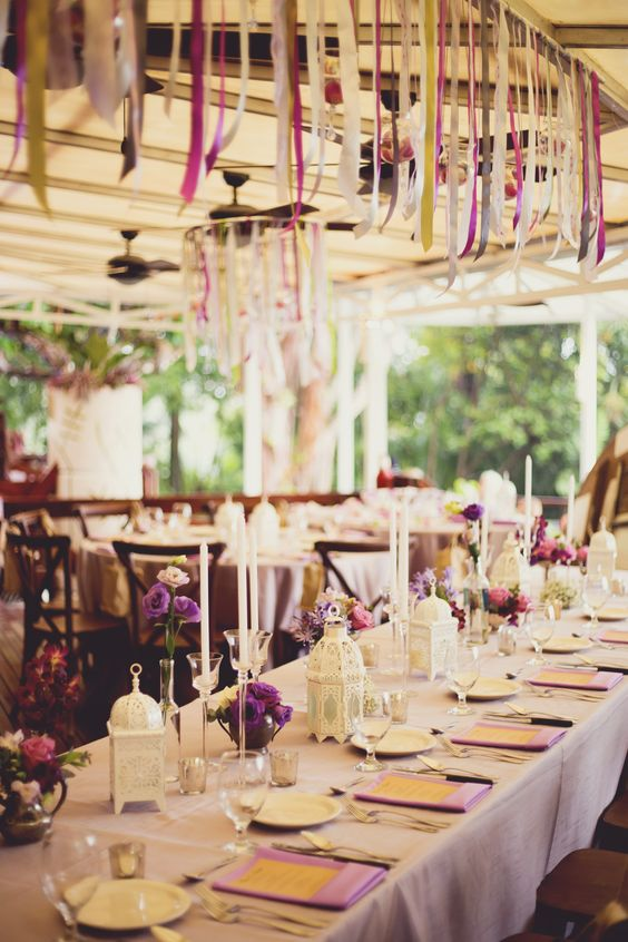 The reception featured a lush table of antique silver pieces filled with lisianthus, roses and agapantos, Moroccan lanterns, candles and colourful ribbons strung overhead.
