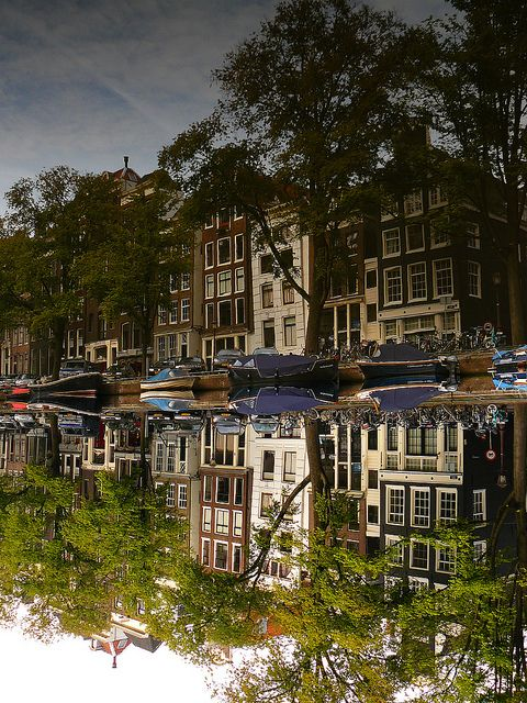 Buildings reflected in the Singel canal, Amsterdam, Netherlands (by AmsterSam).