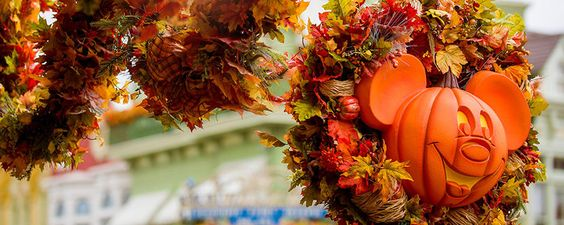 An autumn reef with a Mickey jack o lantern is tied to the top of an old fashioned street lamp