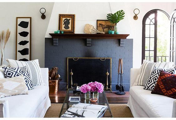 The painted brick fireplace is the focal point of the living room.: