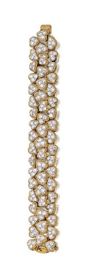 DIAMOND BRACELET, VAN CLEEF & ARPELS, PARIS, CIRCA 1965.  The flexible strap composed of heart-shaped links randomly arranged, set with 206 round diamonds weighing 15.58 carats, mounted in 18 karat gold and platinum, length 7¼ inches, signed V.C.A., made in France, maker's mark, assay marks.