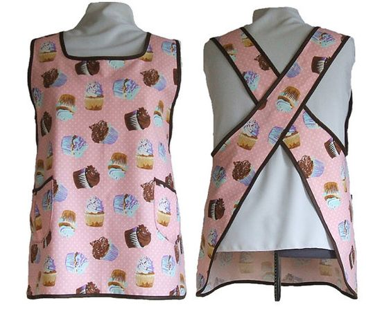 """Very comfortable No ties all day apron, made from cotton duck in pink with cupcakes and polka dots, trimmed in brown bias tape. It is a full coverage front and back with 2 roomy double sewn, lined pockets on the sides. There are no waist ties.  The apron is modeled on a dress form set to 4x. • Length from shoulders is abt. 35"""" • Bust coverage area is 21 • Style #123 • Order #502 • No unfinished seams; everything is bound in bias tape or French lingerie seams. • Ready to wear and ready to…"""