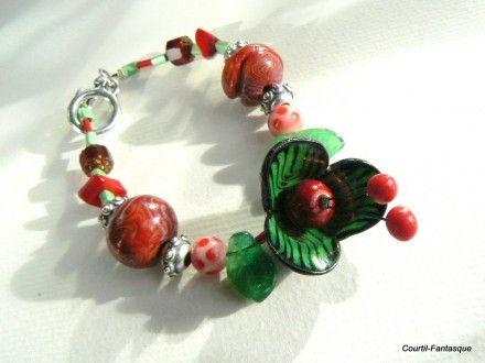Joli bracelet fimo et perles de verre, rouge et vert.  Un bijou de créateur à fleur ronde, montage sur fil câblé très solide. Perles de verre, corail et apprêts plaqués arge - 306343