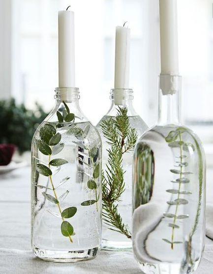 Porte bougie avec bouteille en vert transparente et végétal vert à l'intérieur