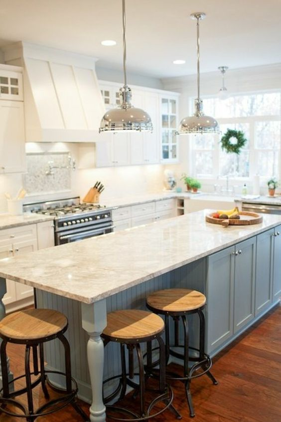 Consider painting a few of the cabinets in your white kitchen your favorite shade of blue. This cool color looks beautiful with warm wood floors and contrasts pleasingly with white marble. #bluekitchen #kitchendesign