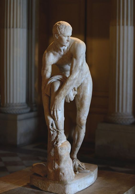 """Hermes fastening his sandal, so-called """"Cincinnatus."""" Pentelic marble. Roman copy of the 2nd cent. CE after a Greek original by Lysippos of the 4th century BCE. Paris, Louvre Museum."""