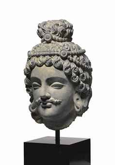 A gray schist head of a bodhisattva  Gandhara, 2nd/3rd century  Finely modeled with bow-shaped mouth and almond-shaped eyes, the hair in heavy locks and secured in a topknot with a jeweled headband 12 in. (30.5 cm.) high