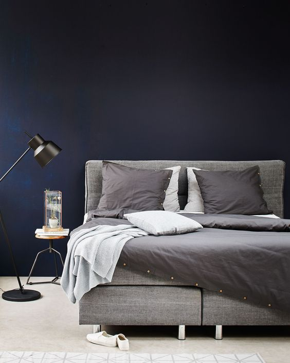 Grey and black bedroom with a grey boxspring bed, grey bedding, off white denim pillow and blanket, a black floorlamp, a wooden stool as a nightstand and a graphic rug   Styling Fietje Bruijn, Marianne Luning, Frans Uyterlinde   vtwonen june 2015   #vtwonenshop