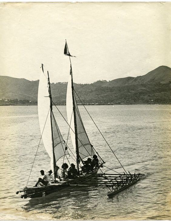 Nine men on an outrigger canoe with sails up; Port Moresby, Papua New Guinea. early 20th