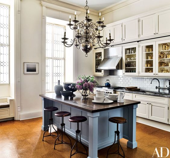 A silver chandelier illuminates the kitchen's butcher-block-top island | archdigest.com