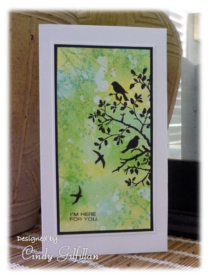 Sponge watercolor panel with various shades of green & golds (& a touch of pale blue), flick water, Dry. Stamp silhouette birds: black ink. Stamp around  edges with other leafy stamps using the same green & blue inks.
