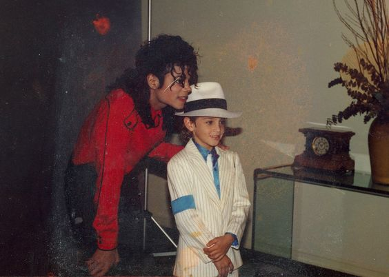 Michael Jackson with a young kid in Neverland