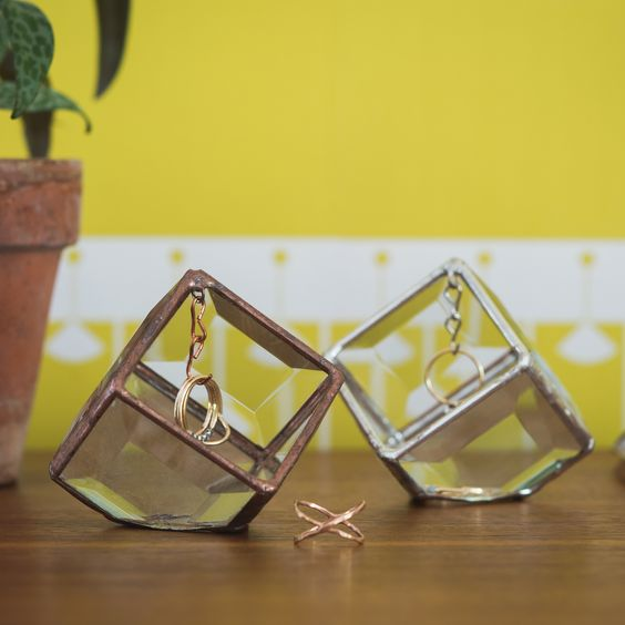 the Prism Ring Box is constructed from beveled glass that create a prism effect in direct sunlight, casting rainbows on nearby surfaces. Poised on its corner, it has a ring soldered into the top tip from where a removable chain hangs down.