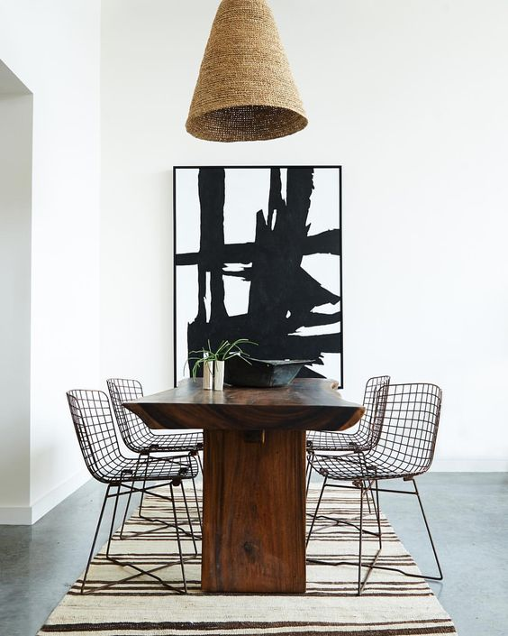A luxurious minimal modern dining room in black and white by Leanne Ford with modern art, wire Bertoia style dining chairs, rustic wood table, and stripe rug. #bertoia #LeanneFord #diningroom