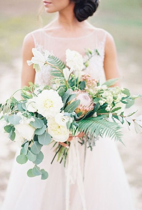Brides.com: . Nectar Floral Designs put together this lush bouquet of creamy dahlias, show-stopping King Protea, mint, eucalyptus, and ferns.