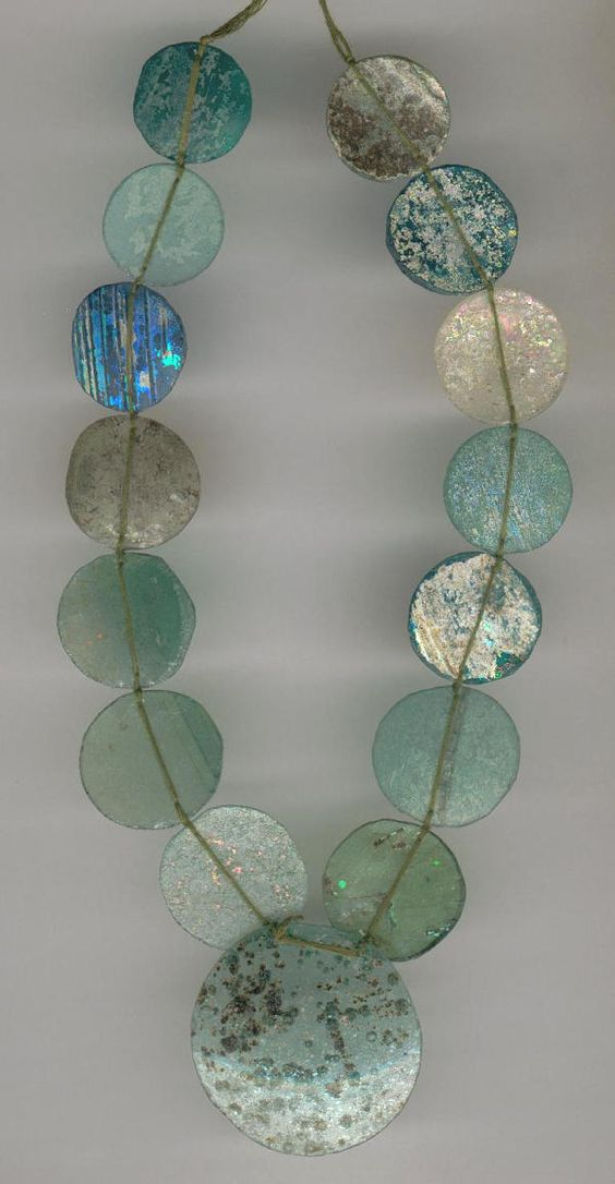 A rare collection of ancient Roman Glass convex discs ~ 200 BC to 400 AD. Found in Afghanistan, they were originally fragments of ancient bottles which have been drilled and rounded into curved discs, displaying a brilliant and multicoloured luminescence resulting from the glass's hundreds of years beneath the ground.