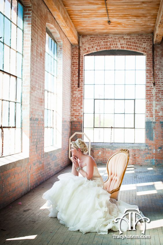bride seated on pink vintage chair in old warehouse with large windows. Photographed by Tracy Autem Photography. http://tracyautem.com