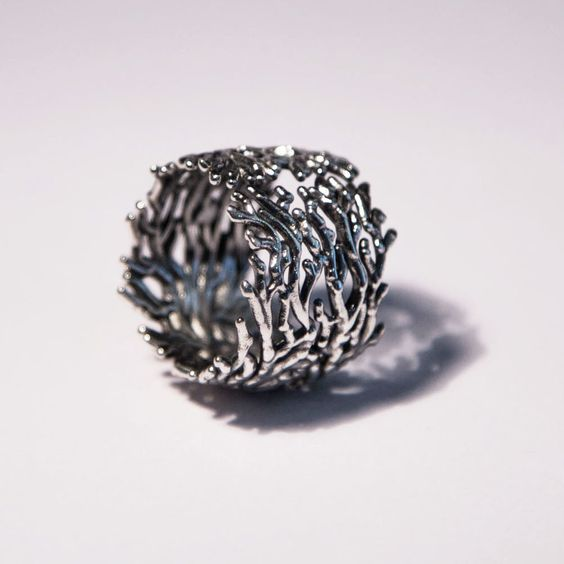 Anello Corallo in Argento 925  Ispirato all'eleganza e perfezione del corallo rosso mediterraneo, viene realizzato in cera persa curando ogni dettaglio, poi rifinito, brunito e lucidato completamente a mano.  La larghezza della fascia dell'anello è di 1,8 cm, ed avvolge comodamente il dito un un luminoso abbraccio.