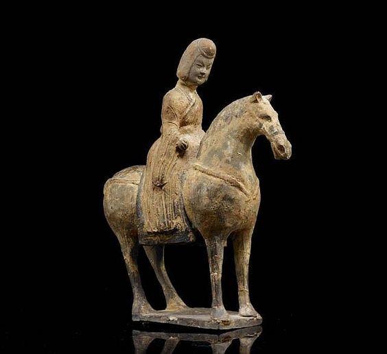 CAVALIER EN TERRE CUITE GRISE, CHINE, DYNASTIE DES WEI (386-557) Représenté à l'arrêt sur une terrasse rectangulaire, le cheval harnaché, le cavalier vêtu d'une robe et portant une coiffe, traces de polychromie carmin ; restaurations aux jambes et la tête du cavalier rapportée H. : 25,3 cm (10 in.)