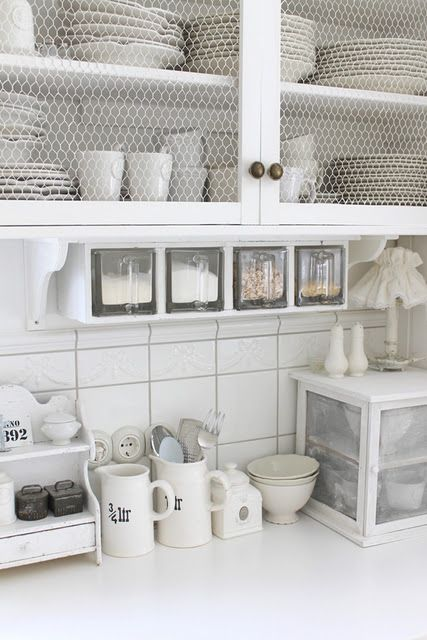 A great country-style feel in bright, crisp white defines this farmhouse kitchen… love the chicken-wire cabinets, and the glass dry go...