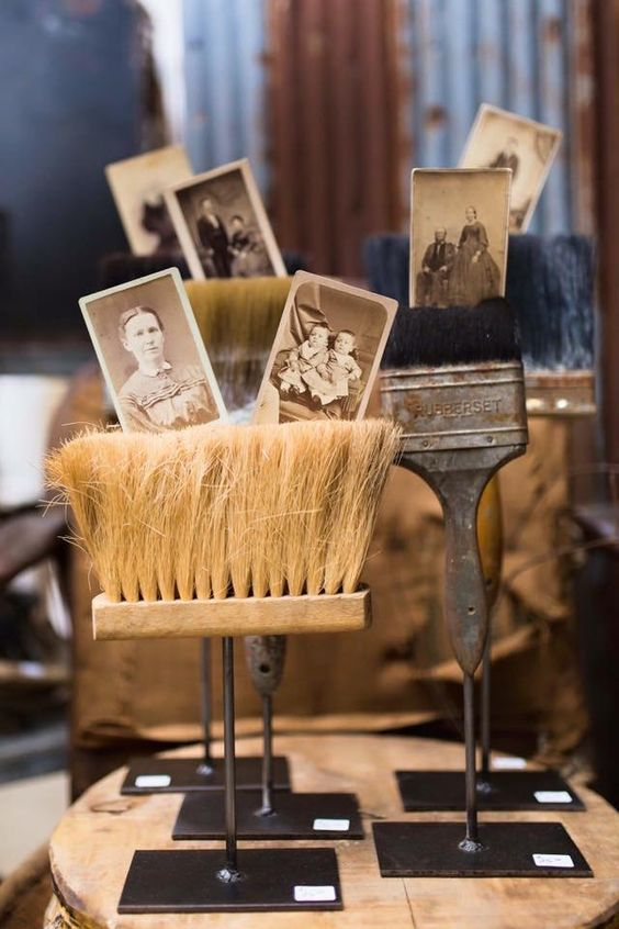 Metal and rusty brooms and paint brushes as photo holders.