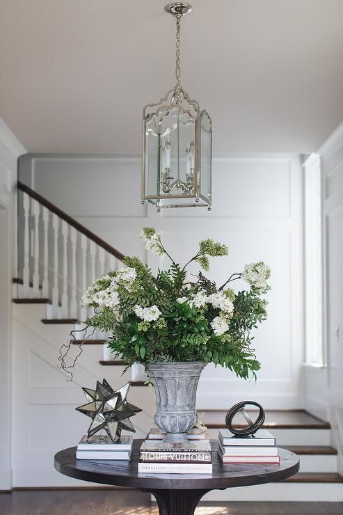 An Arch Lantern Hangs Over A Styled Round Black Wood Entry Table Round Foyer Table Foyer Table Decor Entryway Round Table