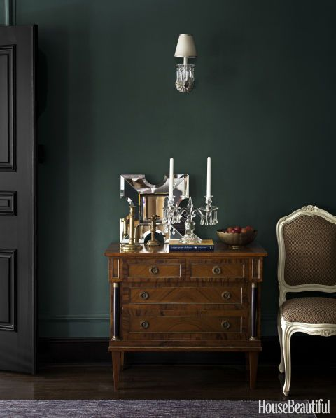 Dining room walls are captivatingly dark in Benjamin Moore's Caribbean Teal. The antique crystal sconce is a Paris flea-market find, and the side chair is upholstered in a Chelsea Editions fabric.