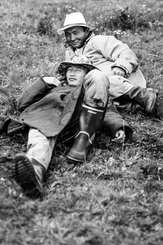 Batjav & Batmagnai lying in the grass, Mongolia - by Mélissa Plantaz