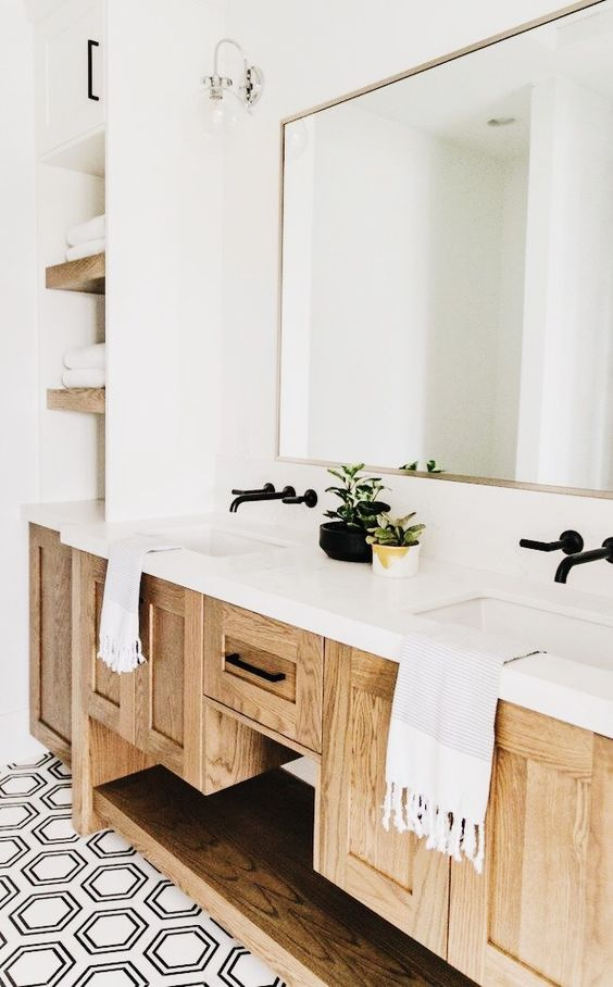 Black faucets set in the wall. White rectangular sinks. Off white counters. Oak cabinets. Black hardware.
