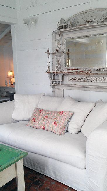 A white sofa and floral pillow in front of a vintage fireplace mantel with over mirror at #ThePrairie by #RachelAshwell