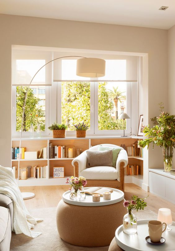 3_Salón pequeño con mesas de centro redondas, butaca, lámpara de pie arqueada y…
