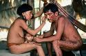 brazil . amazon rainforest . a yanomami woman paints her husband with urucu , the soft seed of a nut stock photo