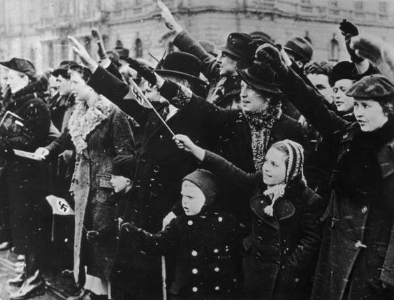 Families in the Moravian city of Brno welcome the Germans with swastika flags and fascist salutes following the Anschluss March 1939