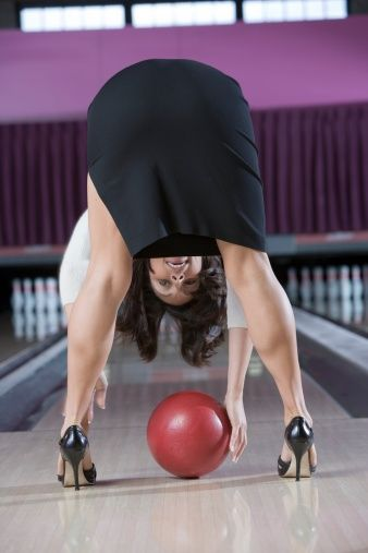 Woman in high heels bending over picking up a bowling ball