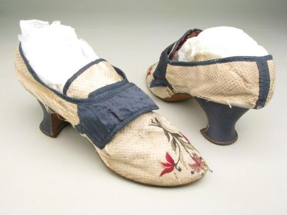 Pair of woman's shoes, 1770-1790. Cream silk woven in small squared pattern. Bound with navy silk ribbon over white linen and kid. Pointed toes with embroidered spray of three flowers in red and green silk and spangles. Fastening with straps and buckle. Tongue lined with purple figured silk. Heel covered with navy silk.