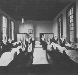 Maagdenhuis Slaapzaal in 1912 (sm) (Bot). Deze slaapzaal lag boven de naaiwinkel (afb. 195). Links zijn de ramen aan het Spui, rechts die aan de binnenplaats. Toen het aantal weeskinderen in de loop van de negentiende eeuw geleidelijk daalde kwam er meer ruimte op de slaapzalen. In plaats van de ouderwetse kribben waarin drie kinderen sliepen werden eenpersoonsbedden ingevoerd. Later werden in de slaapzalen van de oudere meisjes chambrettes gemaakt. #NoordHolland #Amsterdam #wezen #katholiek