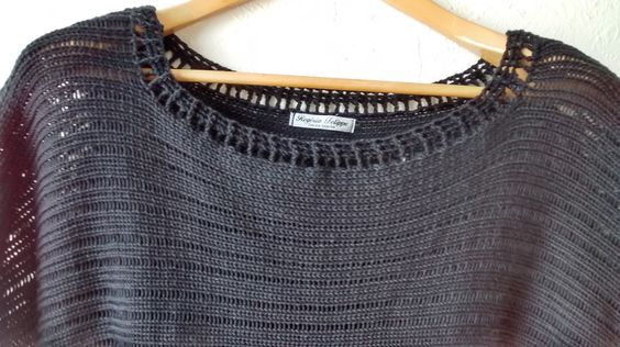 Detalhe barrado da gola em crochê da blusa preta.