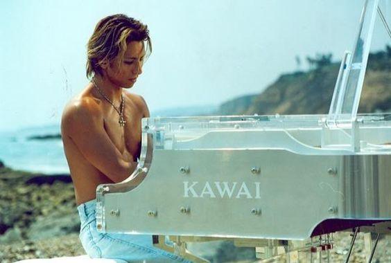 上半身裸でKAWAIのグランドピアノを弾いているXJAPAN・YOSHIKIの画像