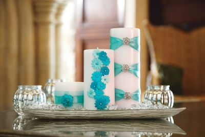 DIY - Embellish candles with jewelry, flowers and ribbon that coordinate with your wedding colors.