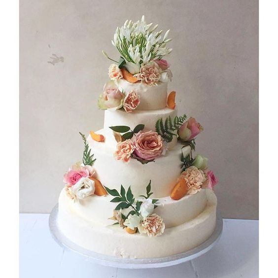 Wedding cake by Lily Vanilli with detail in gold, peach and white