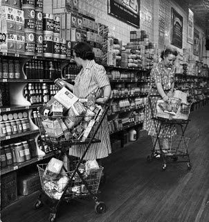 Grocery shoppers loading up their double basket carts in a grocery store with hardwood floors.