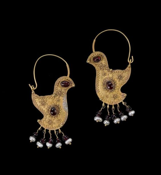 A pair of gold hoop Earrings   Greater Syria or Persia, 10th Century  in the form of birds, with hook and eye clasp, each with garnet set to body and eye, with granluated decoration in the form of sunbursts, a series of four suspensions below with pearl and garnet   both 70 mm. long; total weight 9g: